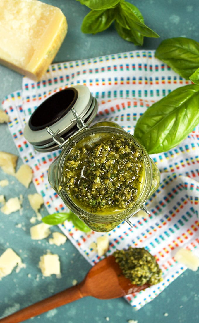 Overhead shot of the Very Best Basil Pesto in a glass jar with a teak spoon on a white napkin from TheSuburbanSoapbox.com