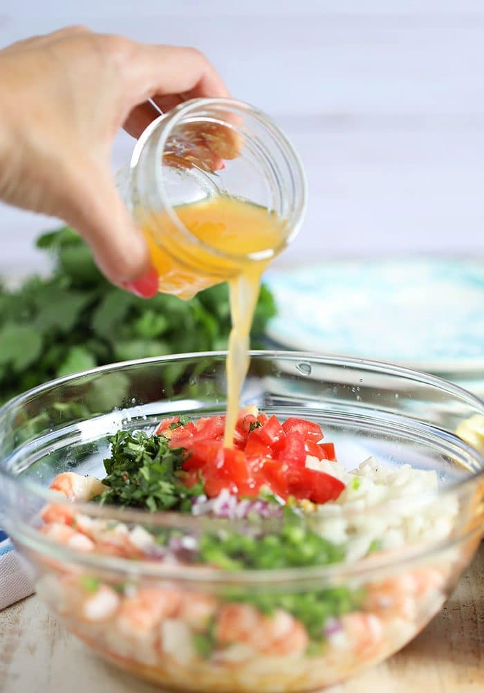 Ingredients for Shrimp Ceviche in a glass bowl with dressing being poured.