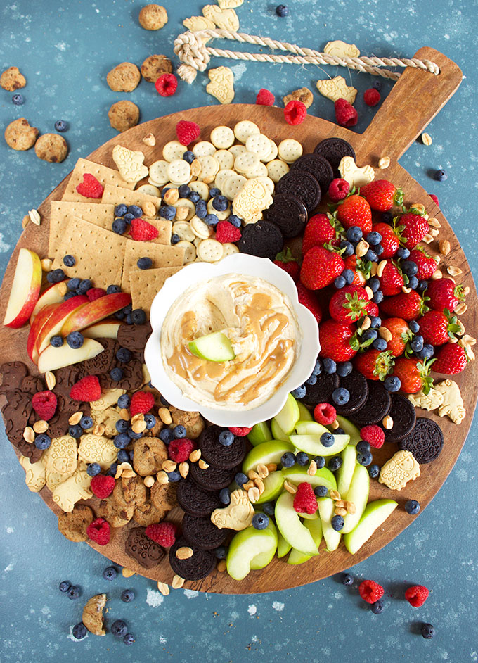 A cookie and fruit charcuterie tray with easy Fluffernutter Dip on a round board on a blue background from TheSuburbanSoapbox.com