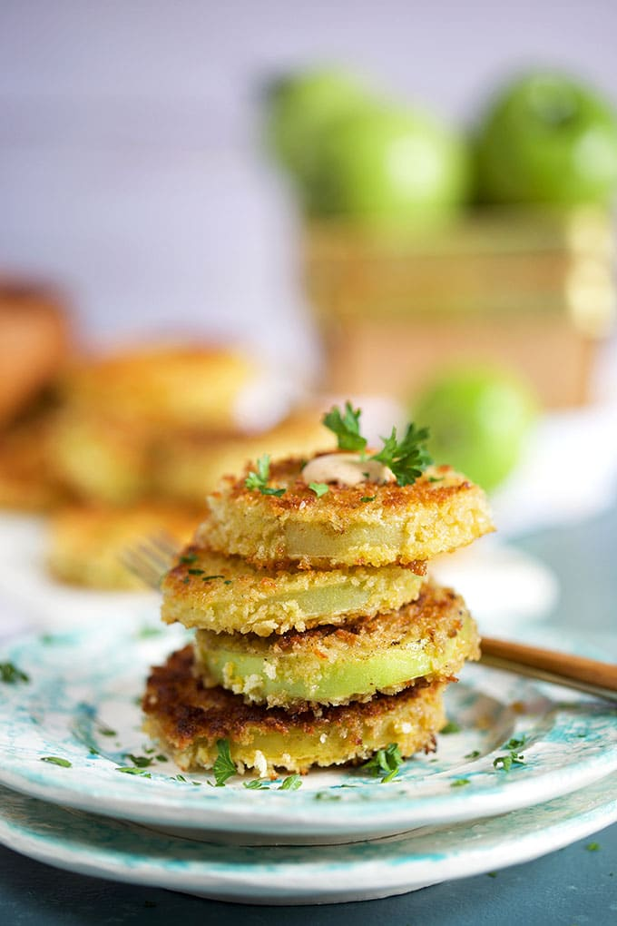 A stack of fried green tomatoes on plates with green tomatoes in the background in a basket from TheSuburbansoapbox.com