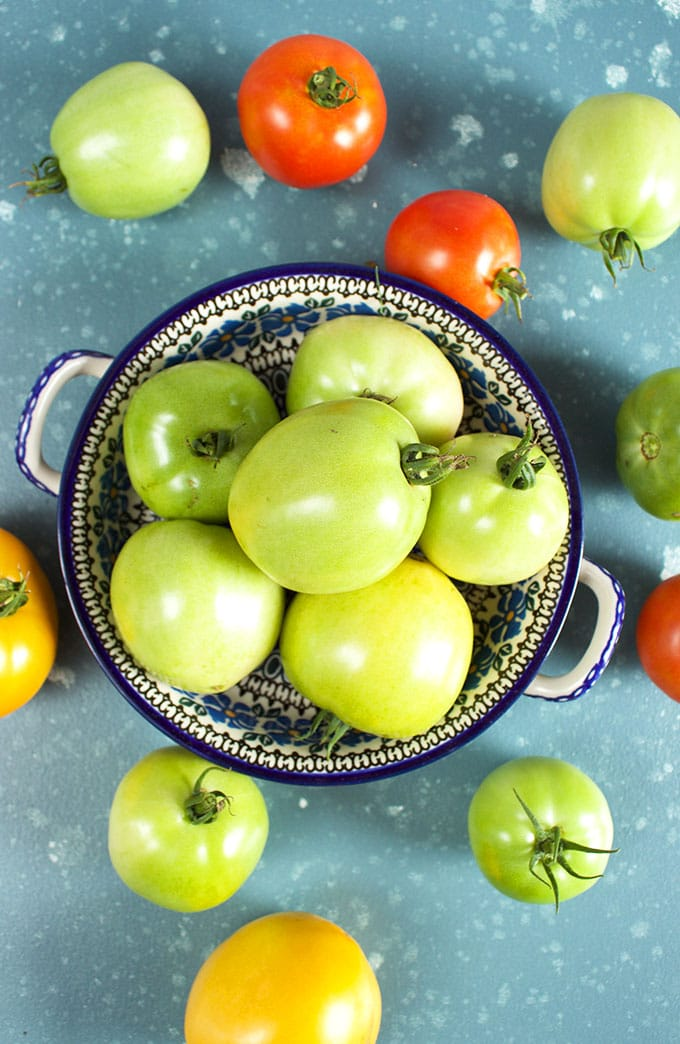 A bowl of green tomatoes on a blue background from TheSuburbansoapbox.com