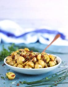 Authentic German Potato Salad in a white bowl with a copper spoon on a blue background from TheSuburbanSoapbox.com