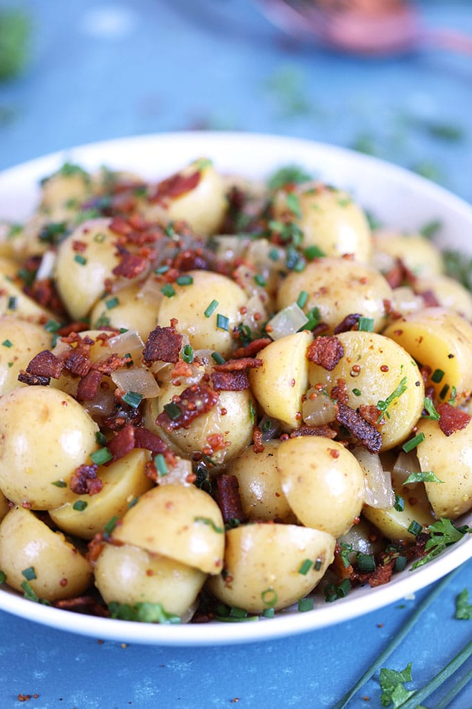 German Potato Salad with bacon in a white bowl on a blue background from TheSuburbanSoapbox.com