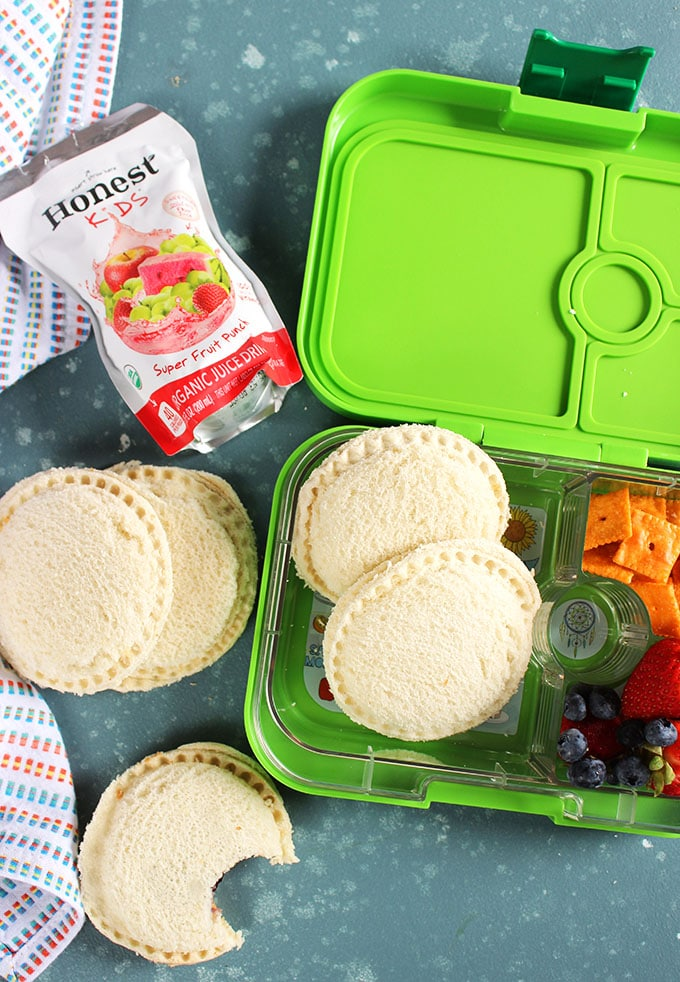 Homemade Uncrustables in a Yumbox with a juice box and strawberries on a blue background from TheSuburbanSoapbox.com