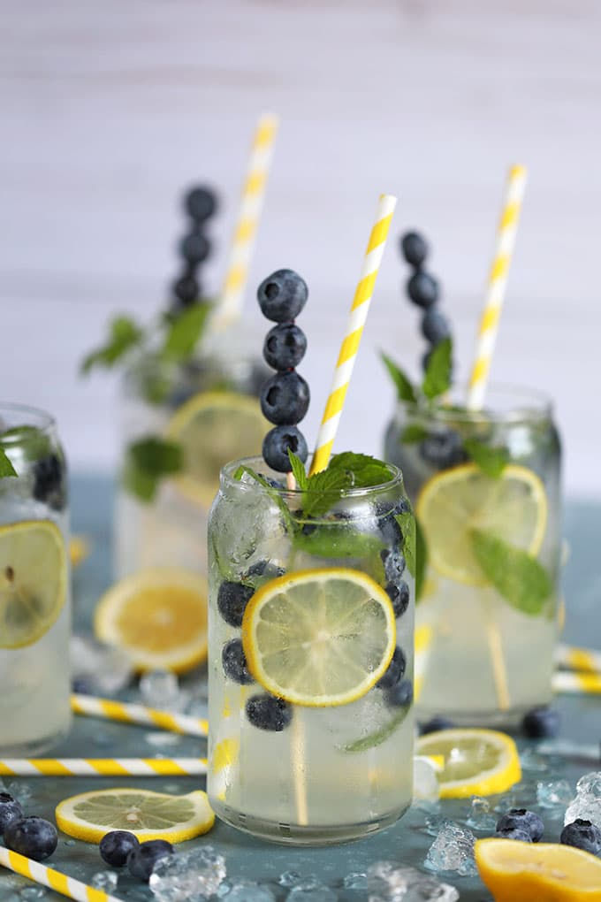 Lemonade Gin Mojito Cocktail in a glass with blueberries on a blue background.