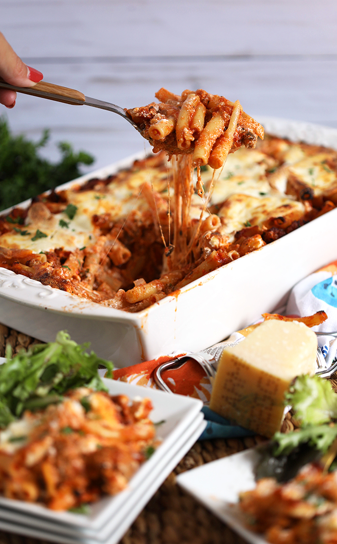 Easy Baked Ziti recipe in a white casserole with a spoonful of ziti with stretchy cheese from thesuburbansoapbox.com