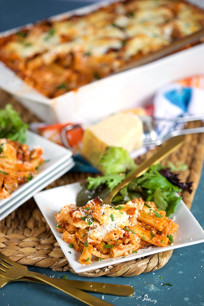 the Very best baked ziti recipe served on a white square plate with a green salad of mixed greens with baked ziti in a white casserole in the background from thesuburbansoapbox.com