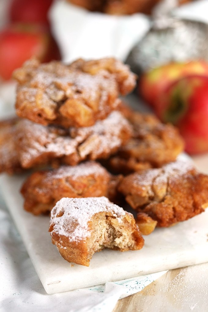 Easy Apple Fritters with powdered sugar on a white marble platter with apples in the background from TheSuburbanSoapbox.com