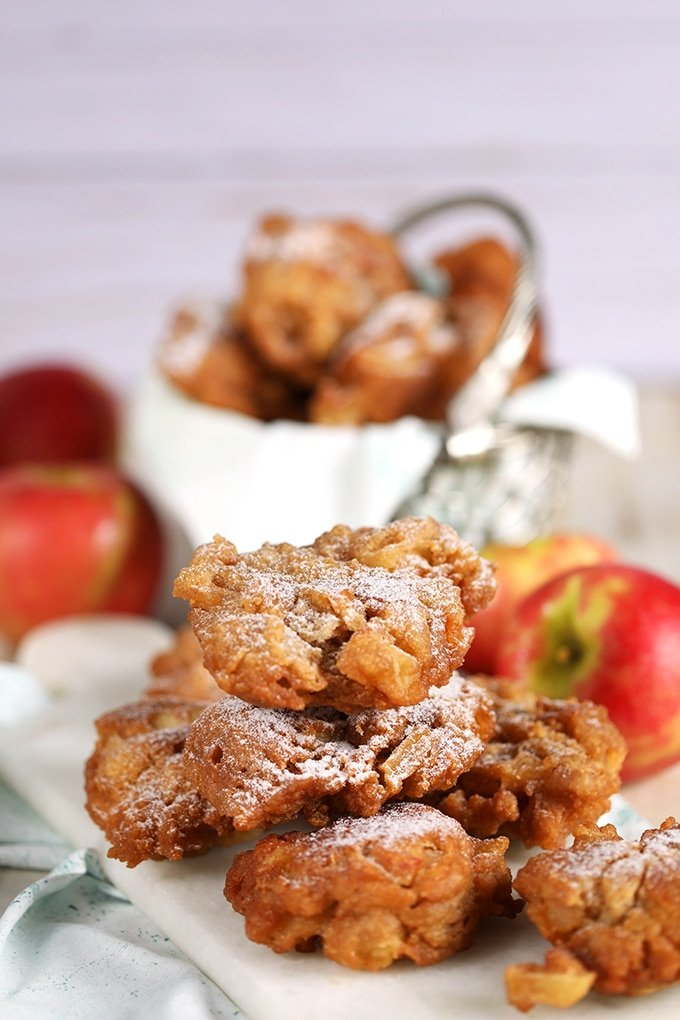 Apple fritters piled in a metal basket with a white napkin.