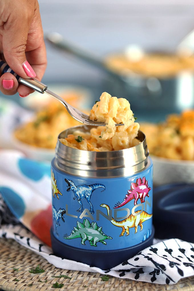 Easy Homemade macaroni and cheese in a blue thermos with dinosaurs on it and a fork digging in to take a bite from TheSuburbanSoapbox.com