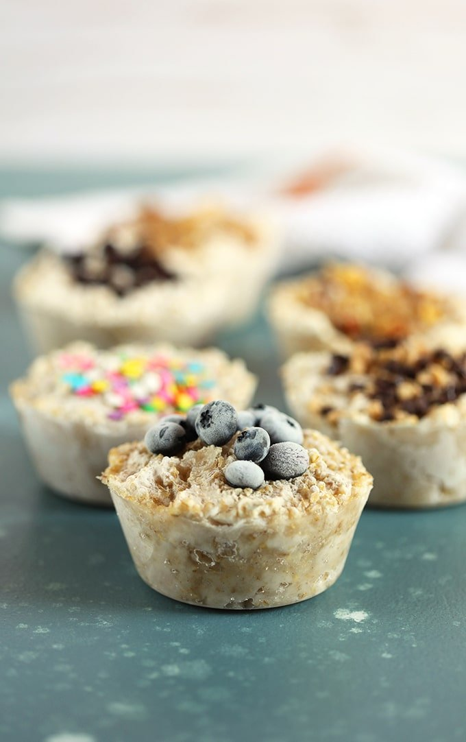 Freezer Oatmeal muffins with various toppings on a blue background from TheSuburbanSoapbox.com