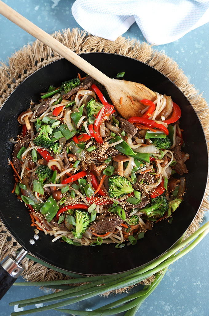 Overhead shot of beef stir fry in a black wok with a wooden spoon.