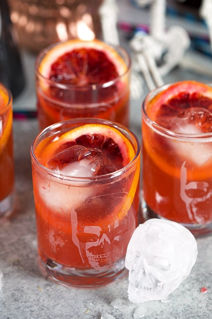 Three glasses with skulls on them with Blood Orange Dark and Stormy Cocktails and a skull ice cube.