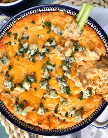 Overhead shot of Buffalo Chicken Dip recipe made from scratch with two crackers and a celery stick.