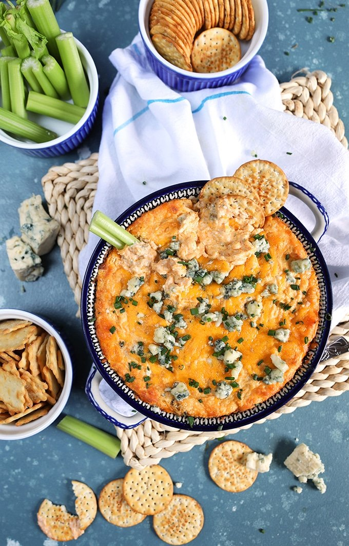 Overhead shot of buffalo chicken dip in a floral dish with celery, carrots and crackers around on a blue background.