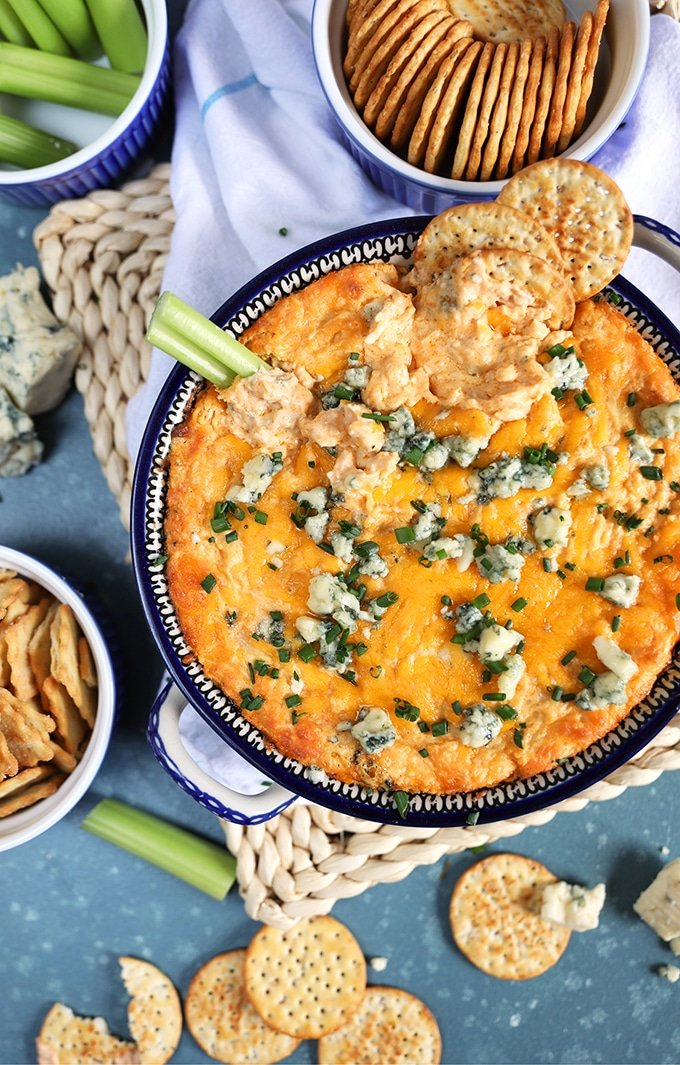 Overhead shot of buffalo chicken dip with blue cheese and crackers on top on a blue background.