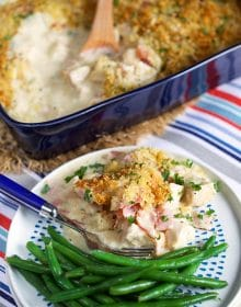 A plate with a serving of chicken cordon bleu casserole with green beans and a blue fork.