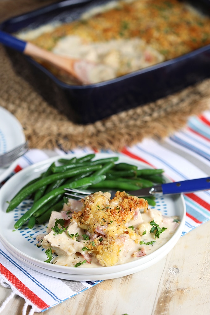 Chicken Cordon Bleu Casserole on a white plate with green beans.