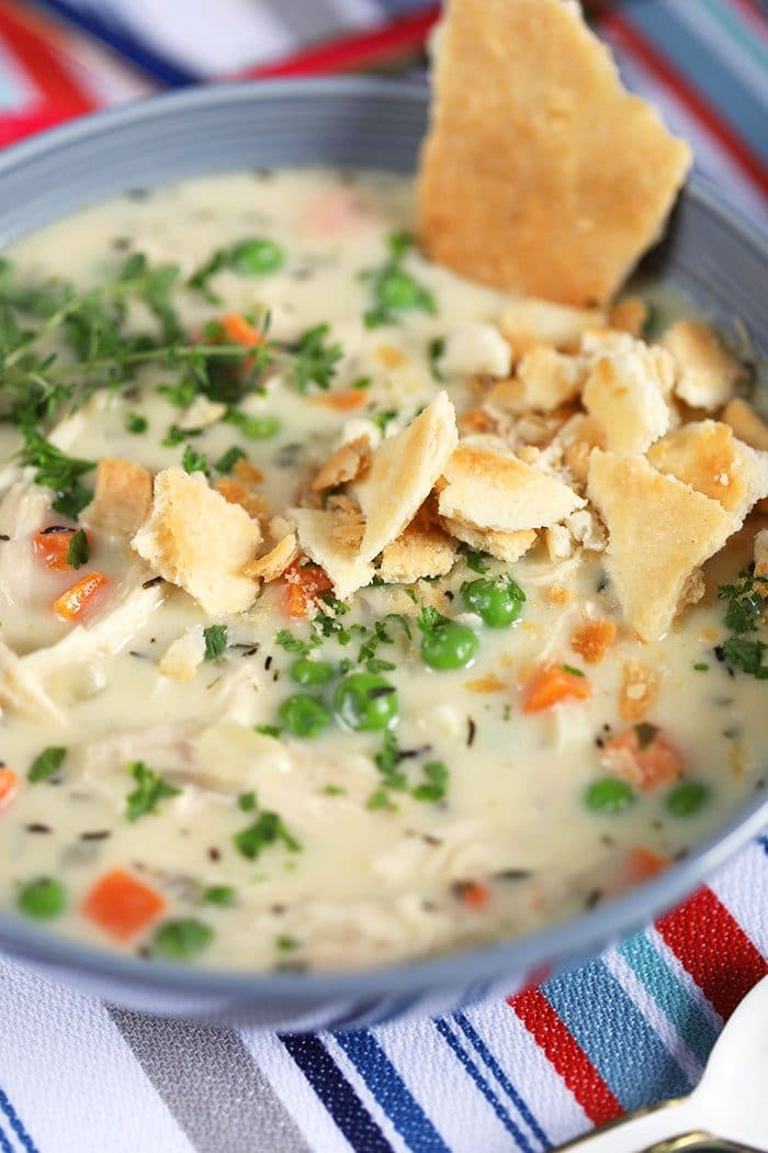 Close up overhead shot of Chicken Pot Pie soup with crumbled pie crust, peas and carrots on a striped tablecloth.