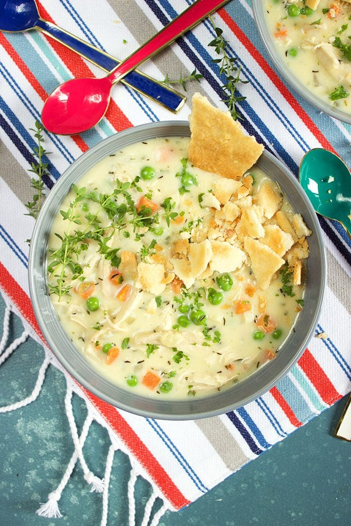 Overhead shot of one blue bowl of chicken pot pie soup on a striped tablecloth from TheSuburbanSoapbox.com