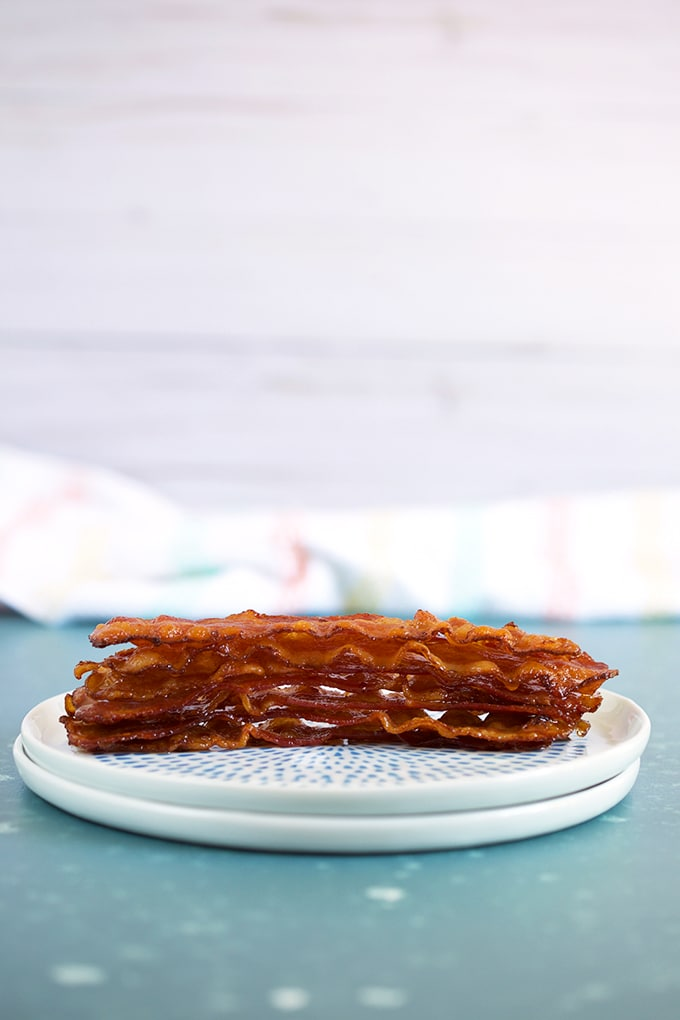 8 stacked bacon slices on a white plate on a blue background.