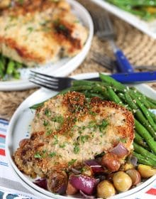 Parmesan Crusted Baked Pork Chops with green beans and potatoes on a white plate with a blue fork.