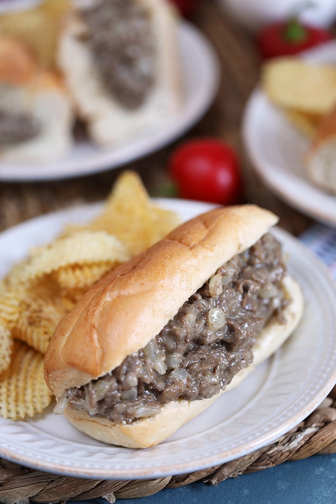 Philly cheesesteak sandwich on a white plate with chips.
