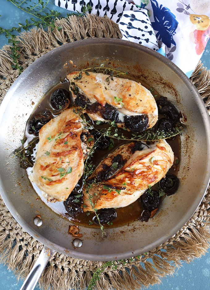 Overhead shot of three stuffed chicken breasts in a stainless steel skillet on a blue background.