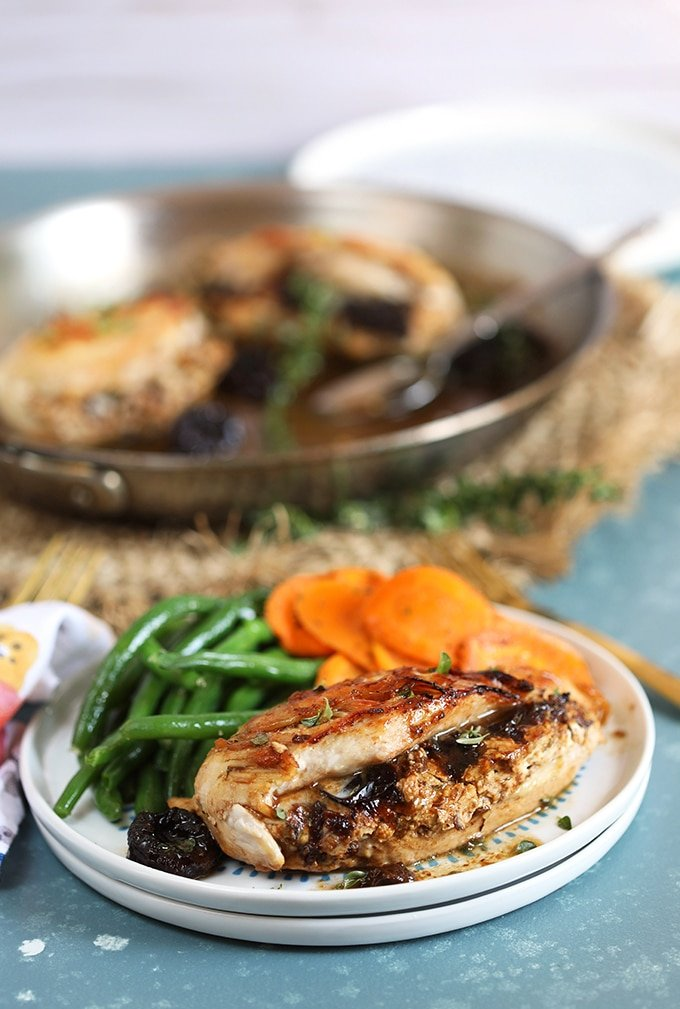 Goat Cheese Stuffed Chicken Breast on a white plate with green beans and carrots with a skillet full of chicken in the background.