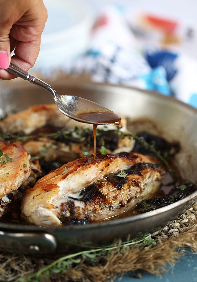 Goat Cheese Stuffed Chicken Breast in a skillet being basted with fig pan sauce.