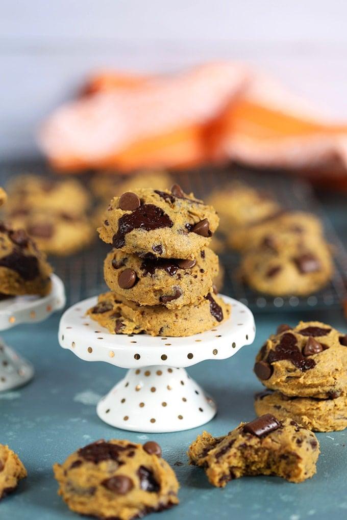 Three pumpkin chocolate chip cookies on a white cupcake stand.