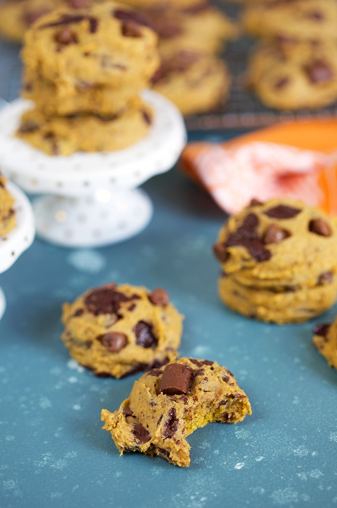Pumpkin chocolate Chip cookies on a blue background with an orange tea towel and a white cupcake stand with cookies stacked on top.