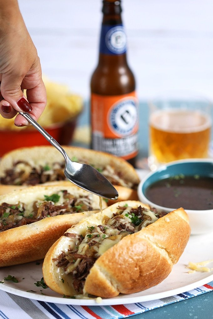 French Dip Sandwich on a white platter being drizzled with au jus from a silver spoon.