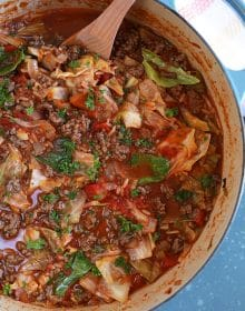 Close up overhead shot of Stuffed Cabbage Soup in a blue pot with a wooden spoon.