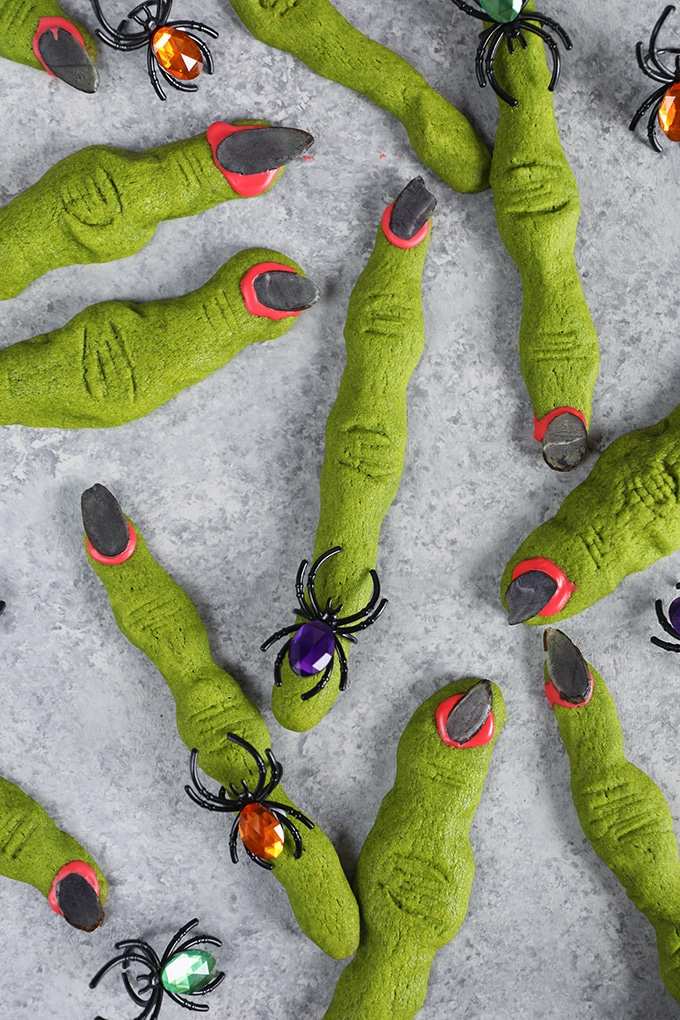 Overhead shot of many witch finger cookies on a gray background wearing spider rings.