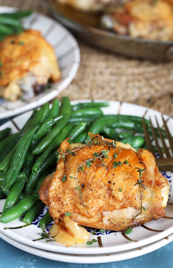 Close up of Crispy Baked Chicken Thighs on a white plate with green beans on a blue background.