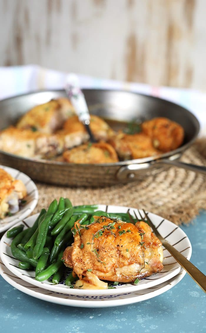 Crispy Baked Chicken Thighs on a white plate with green beans from TheSuburbanSoapbox.com
