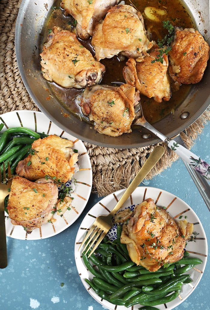 Overhead shot of Crispy Baked Chicken Thighs in a skillet with two white plates with chicken and green beans on a blue background.