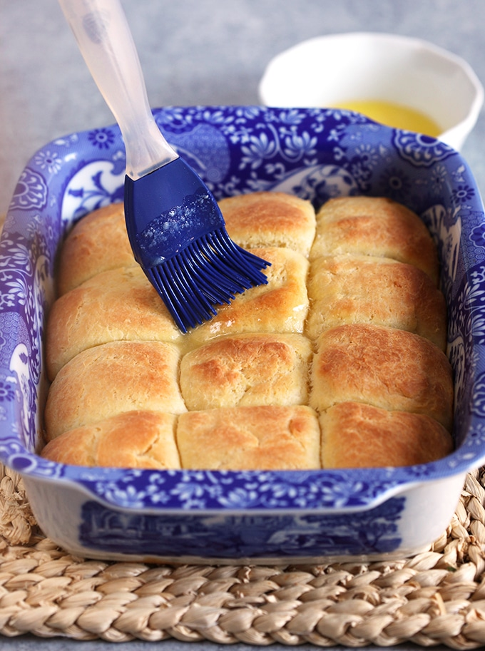 Dinner rolls in a baking dish after baking with a blue brush basting with butter.