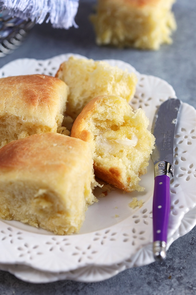 Dinner rolls on a white plate with a purple spreader with butter.