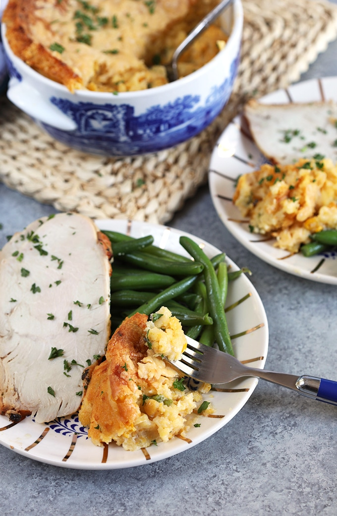 Cheesy Corn Casserole on a white plate with turkey and green beans.