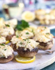 Crab stuffed mushrooms on a white board with lemons.
