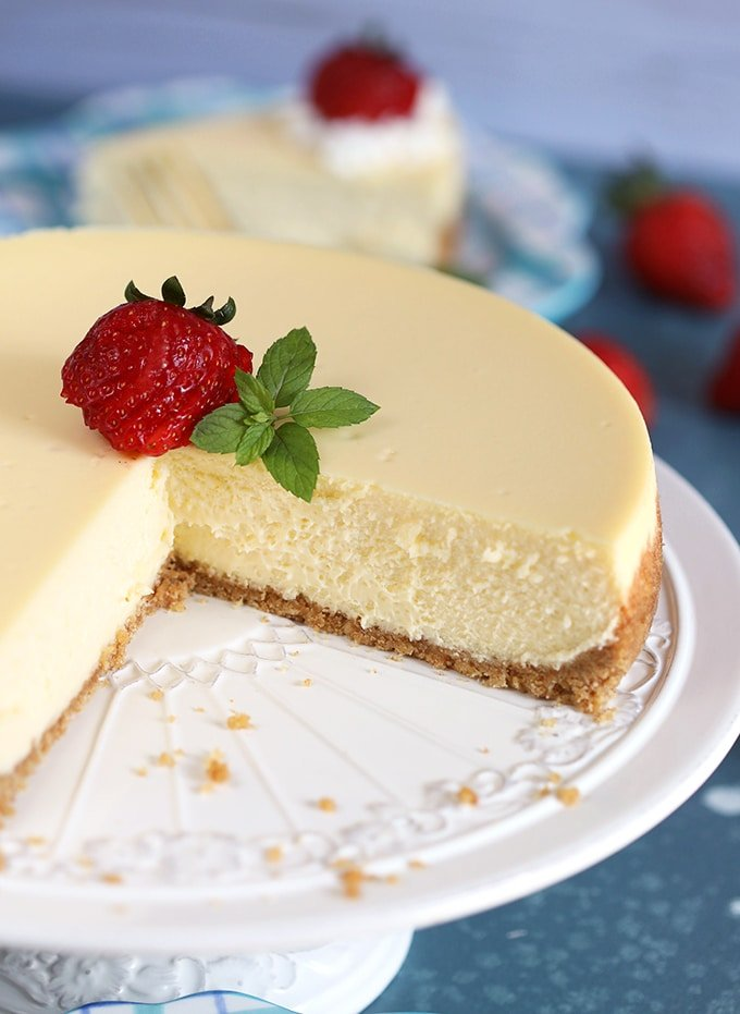 Close up of whole New York Cheesecake with a slice taken on a white cake plate.
