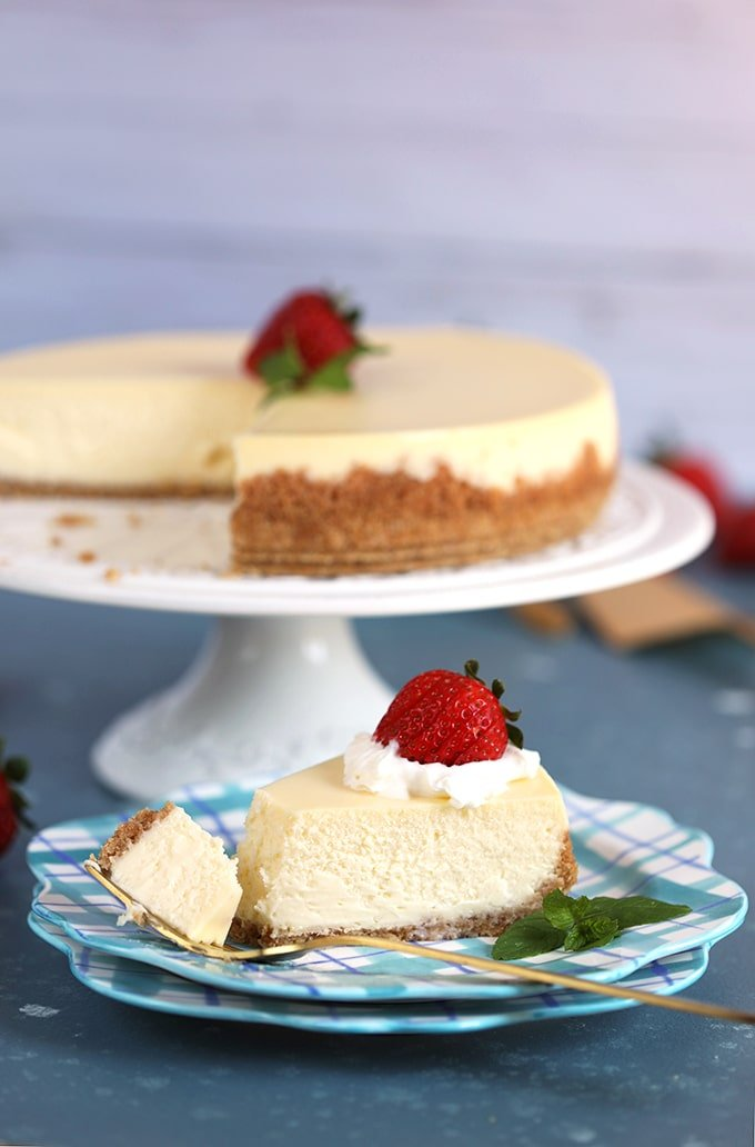 Shot of whole New York Cheesecake with a slice on a plaid plate and a fork with a bite taken.