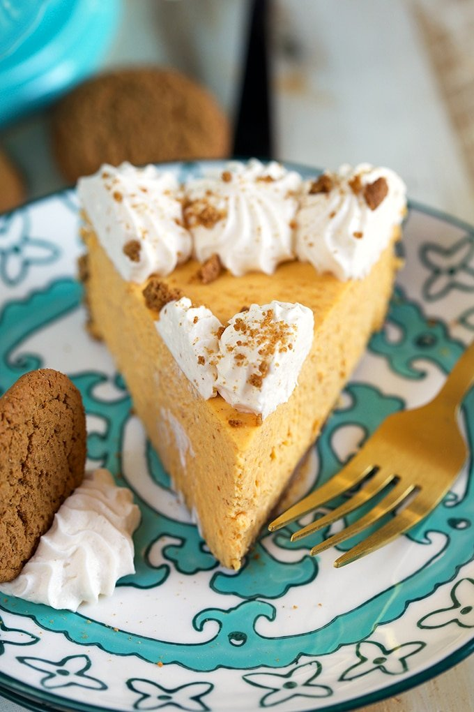Slice of Pumpkin cheesecake on a decorative plate with a gold fork.
