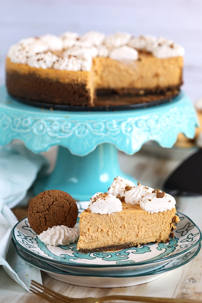 Pumpkin Cheesecake on an aqua cake plate with a slice of cheesecake on a plate in front of it.