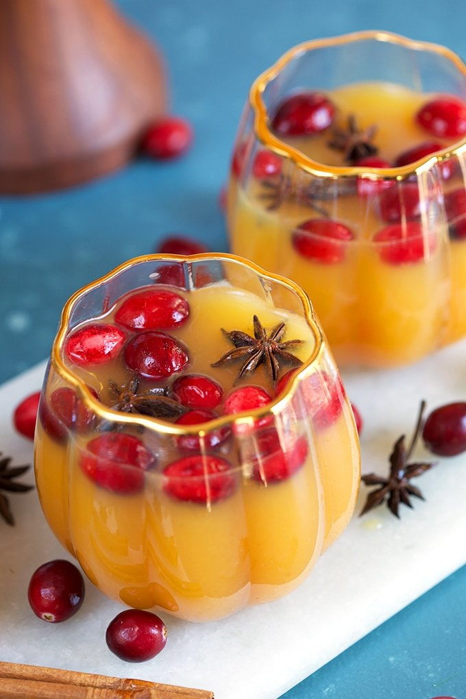Pumpkin punch in pumpkin glasses with cranberries and star anise floating on top.