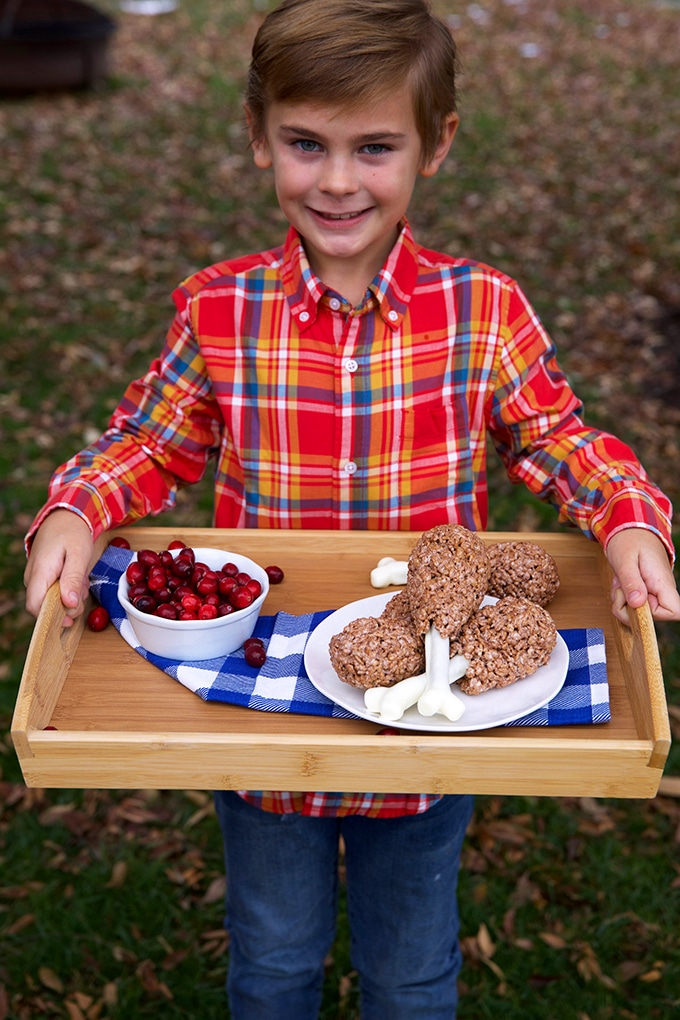 Boy holding a tray with Rice Krispie treat turkey legs and cranberries.