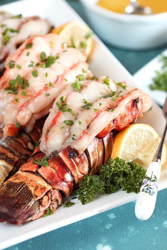 Baked lobster tails on a white platter with lemon and parsley.