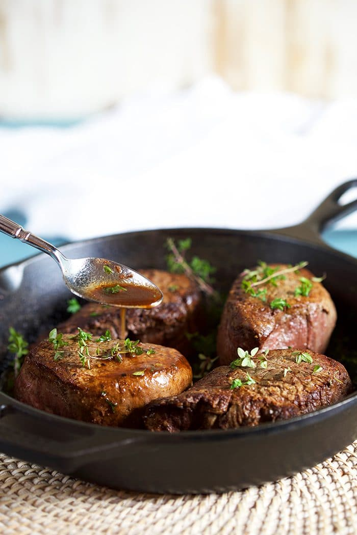Pan juices being drizzled over filet mignon in a cast iron skillet.